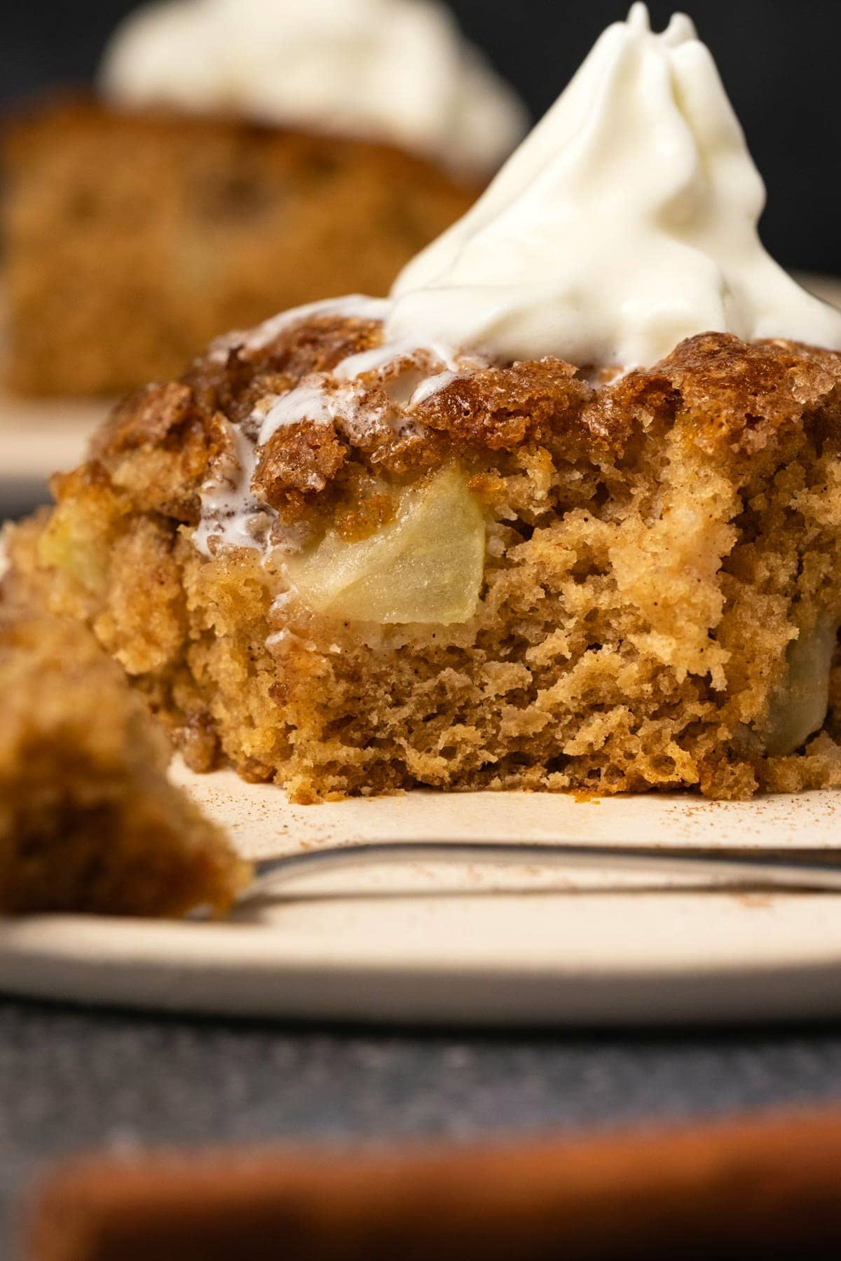 Slice of apple cake topped with melting whipped cream.