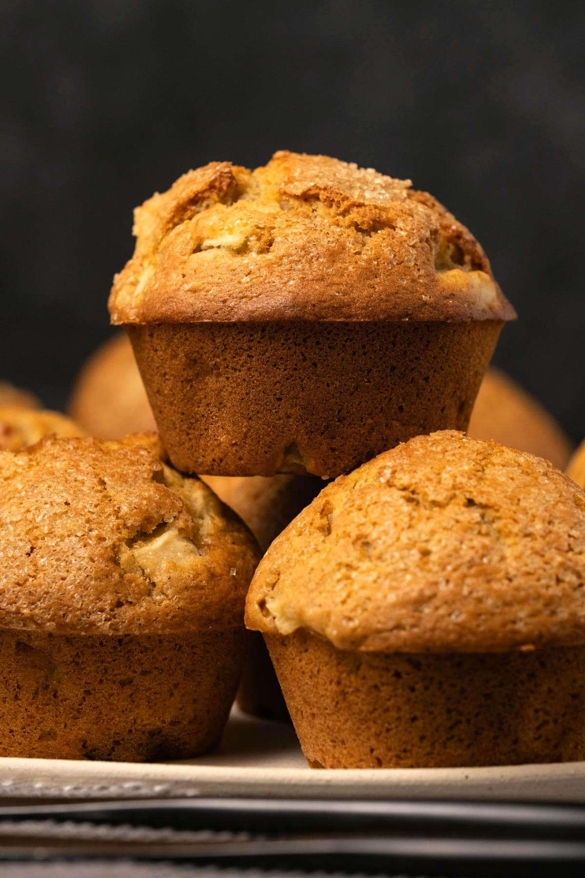 Apple muffins in a stack on a plate.