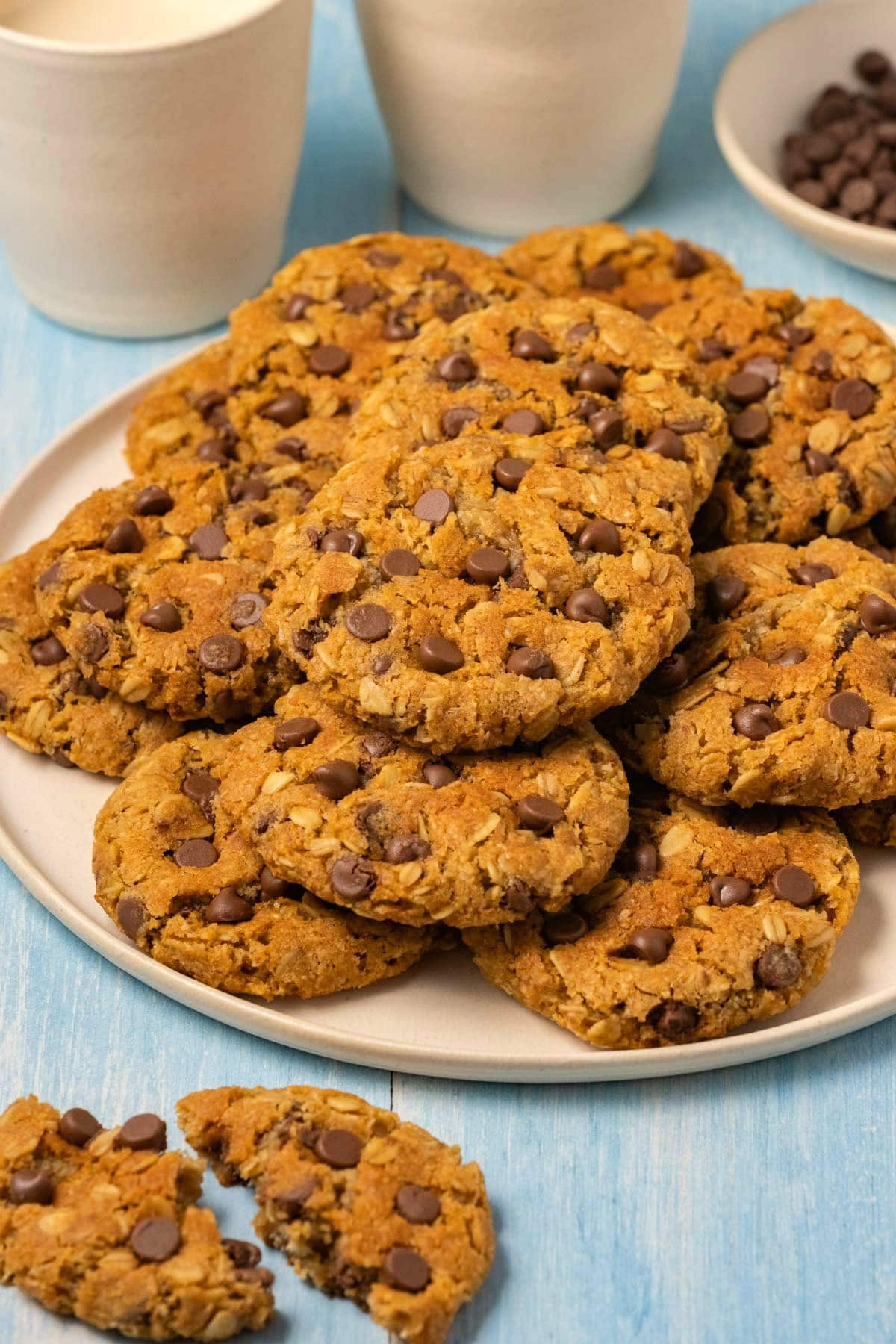 Oatmeal chocolate chip cookies stacked up on a plate.