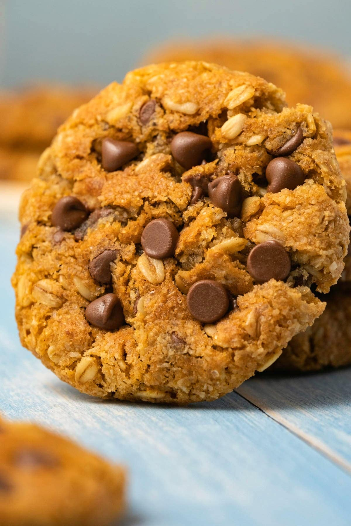 An oatmeal chocolate chip cookie leaning against a stack of cookies.