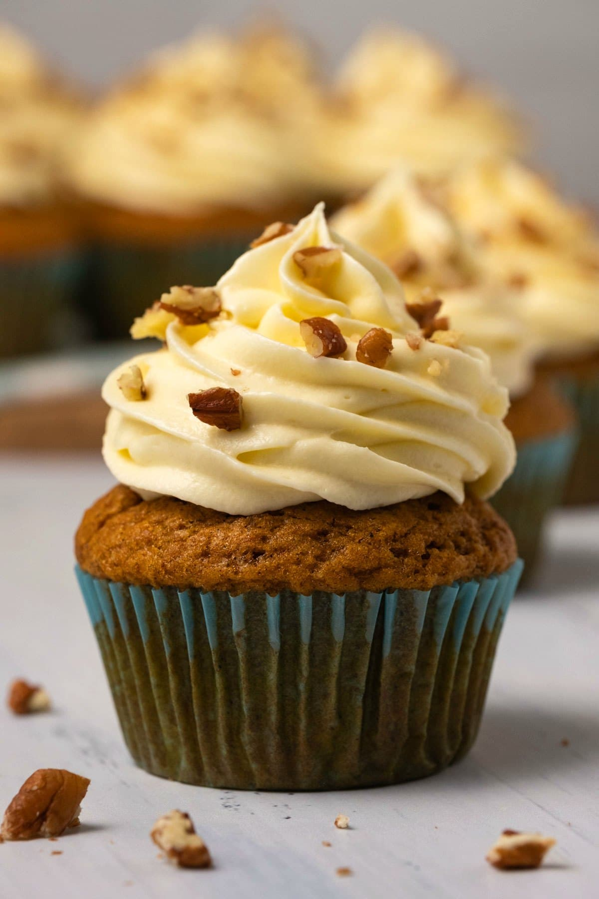 Pumpkin cupcake with cream cheese frosting and chopped pecans.