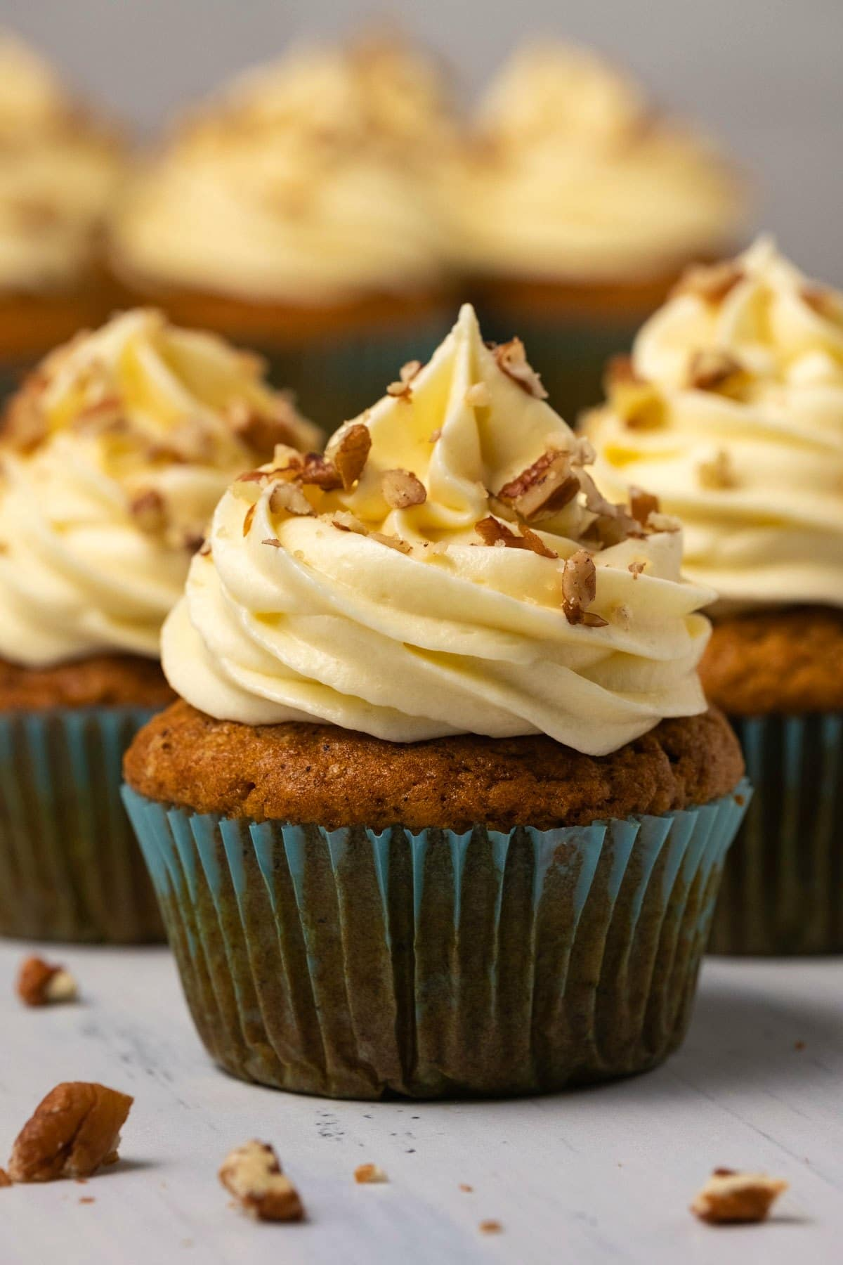 Pumpkin cupcakes topped with cream cheese frosting and chopped pecans.