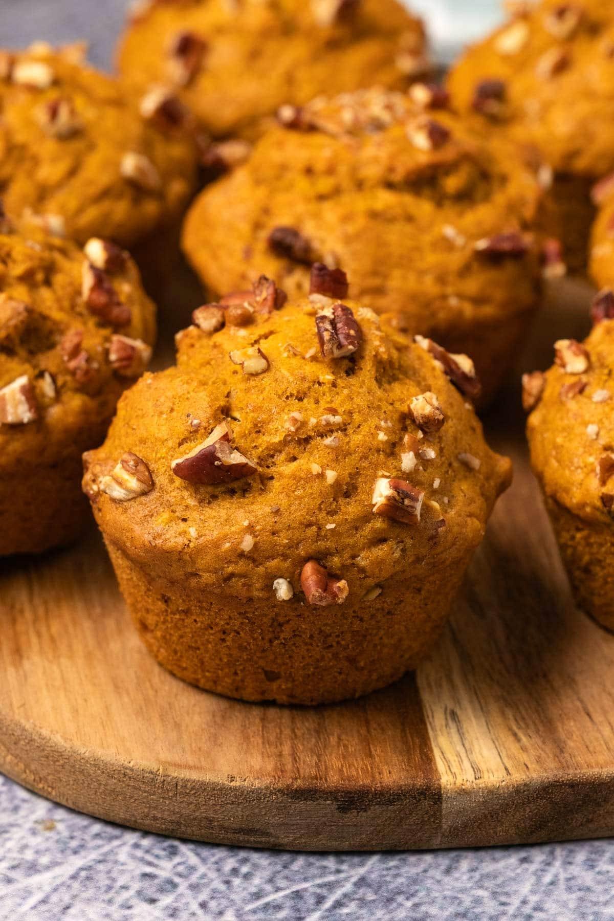 Pumpkin muffins on a wooden board.