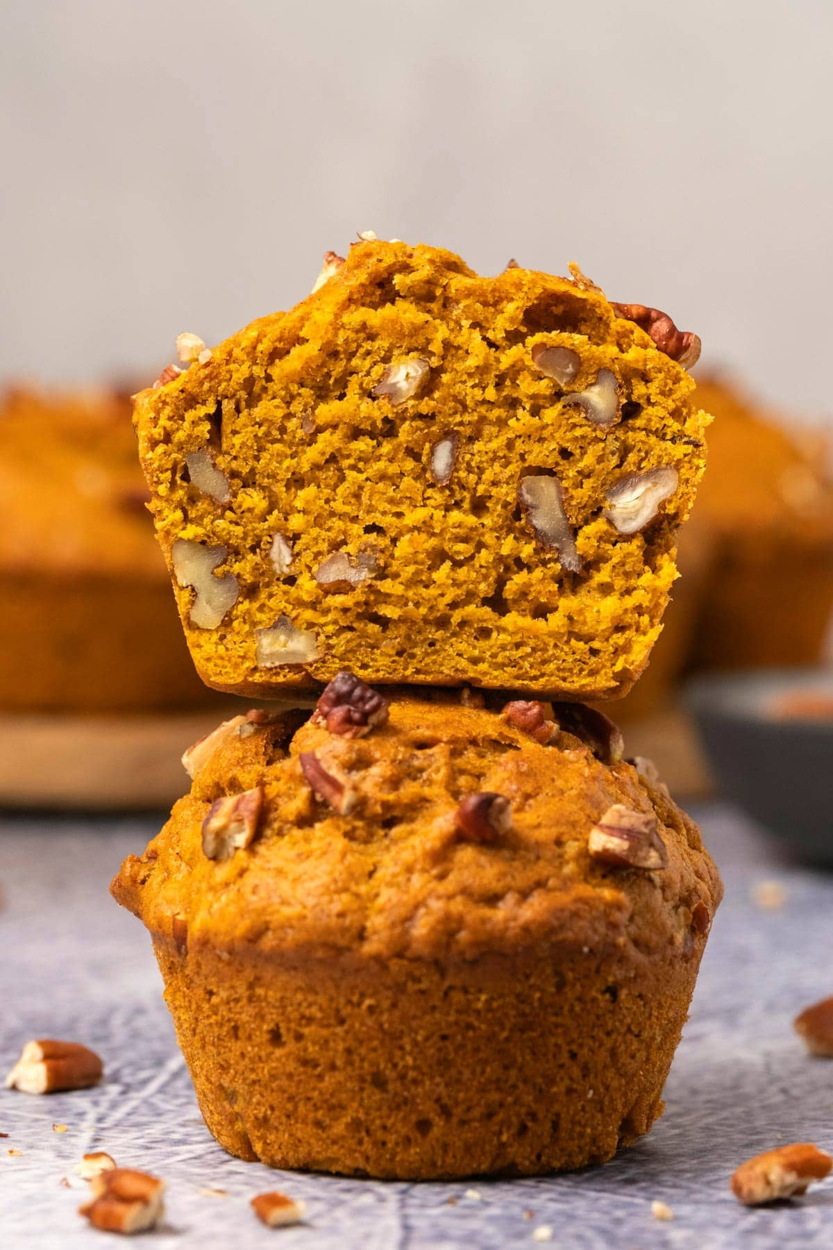 Pumpkin muffins in a stack with the top muffin cut in half.