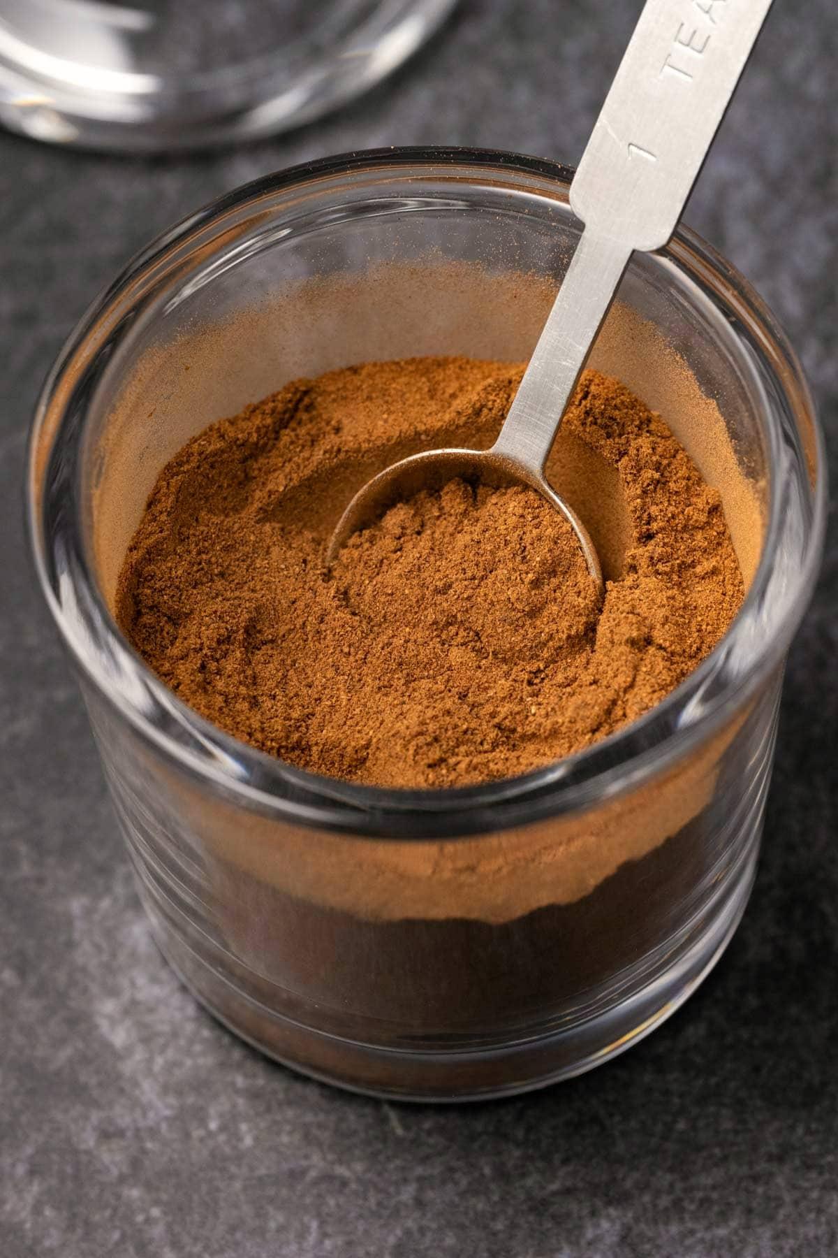 Pumpkin pie spice in a glass jar with a spoon.