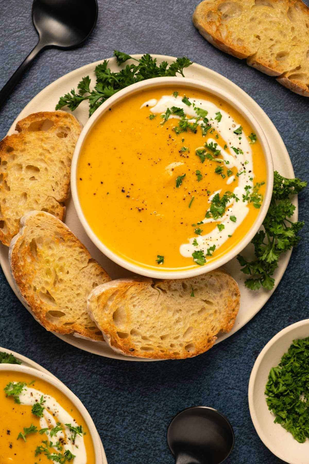 Sweet potato soup with fresh chopped parsley in a bowl.