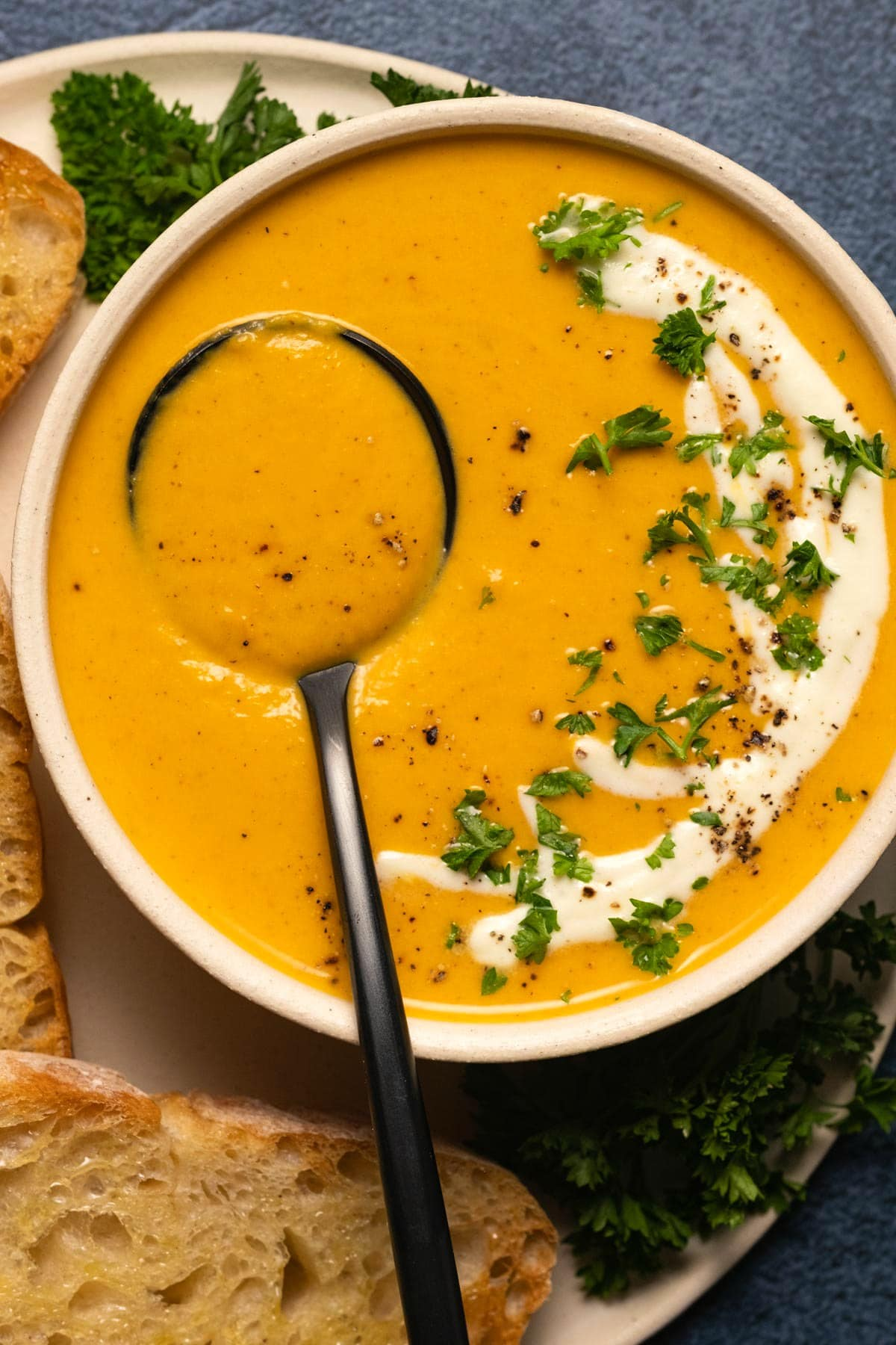 Sweet potato soup with cream and fresh parsley in a white bowl with a spoon.