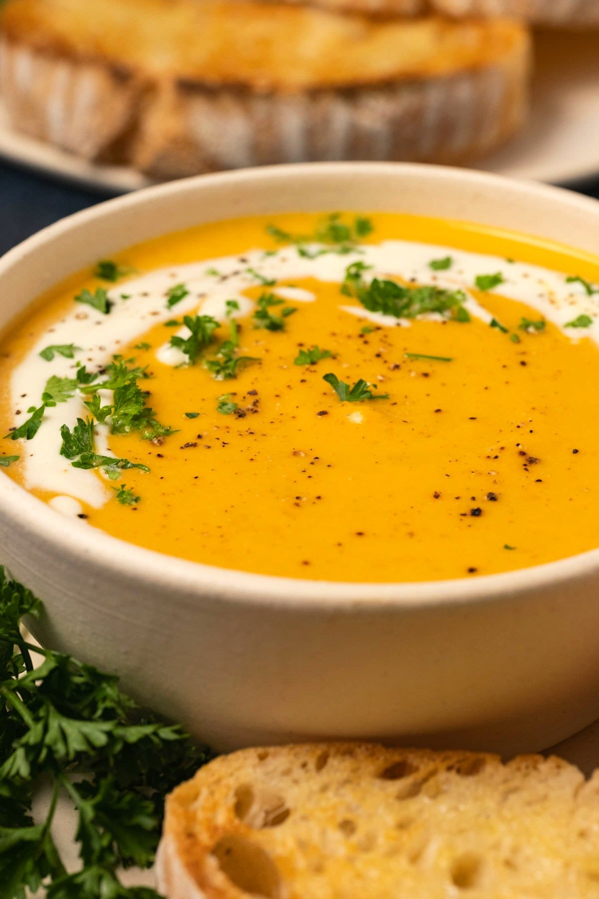 Sweet potato soup with fresh chopped parsley and cream in a bowl.