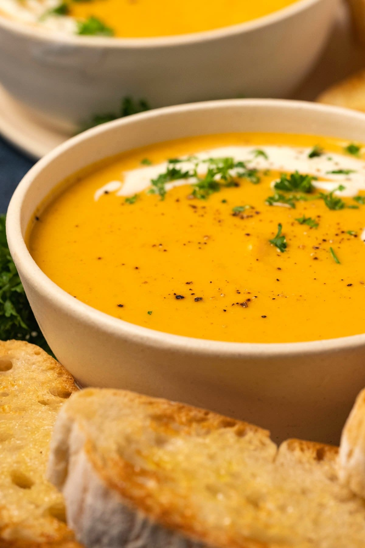 Sweet potato soup with cream and fresh parsley in a white bowl.