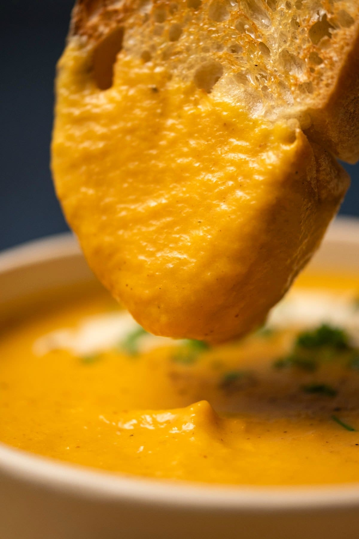 Slice of bread dipping into a bowl of sweet potato soup.