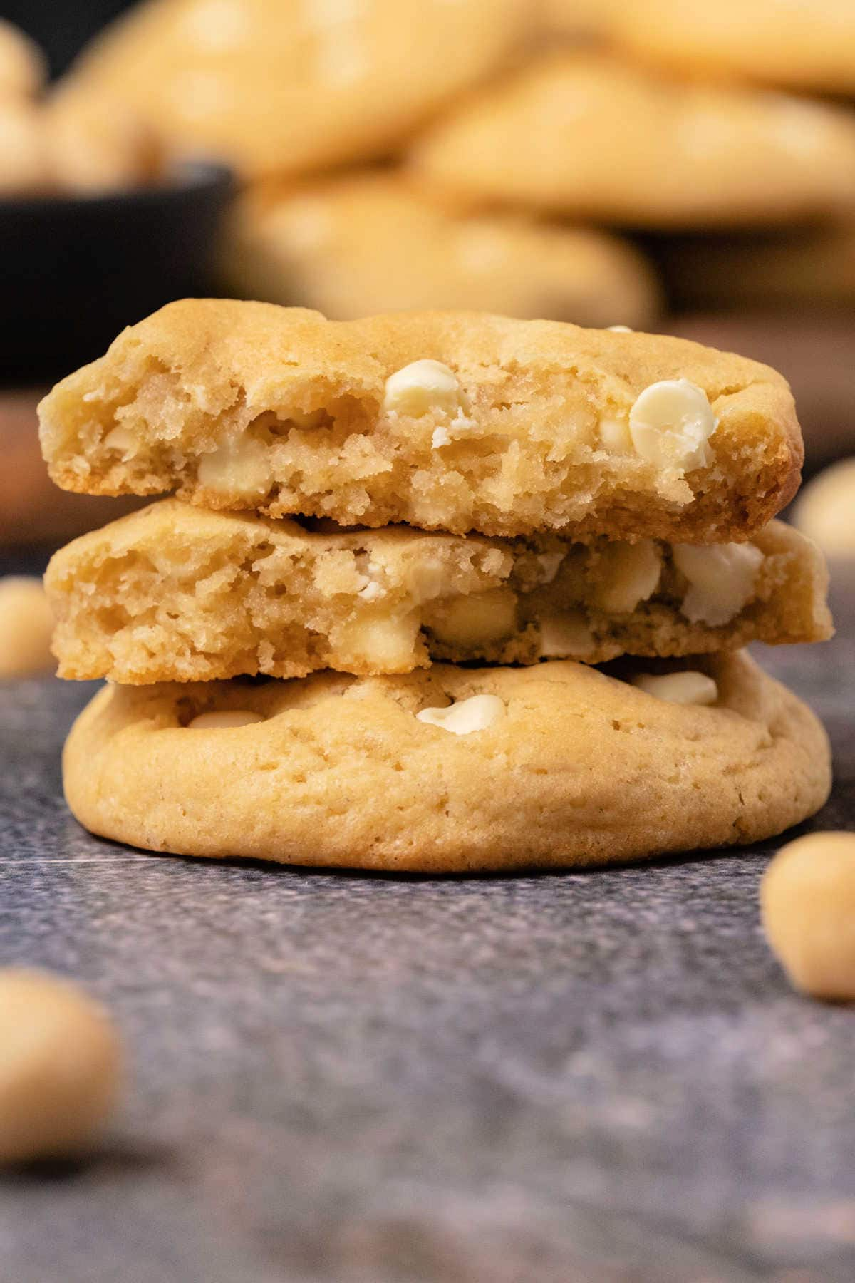Macadamia nut cookies in a stack with the top cookie broken in half.