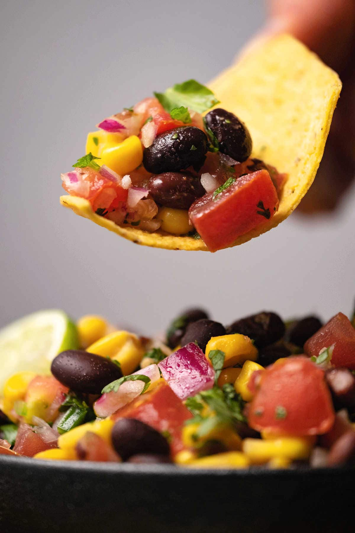 Corn chip scooping up a serving of black bean salsa.