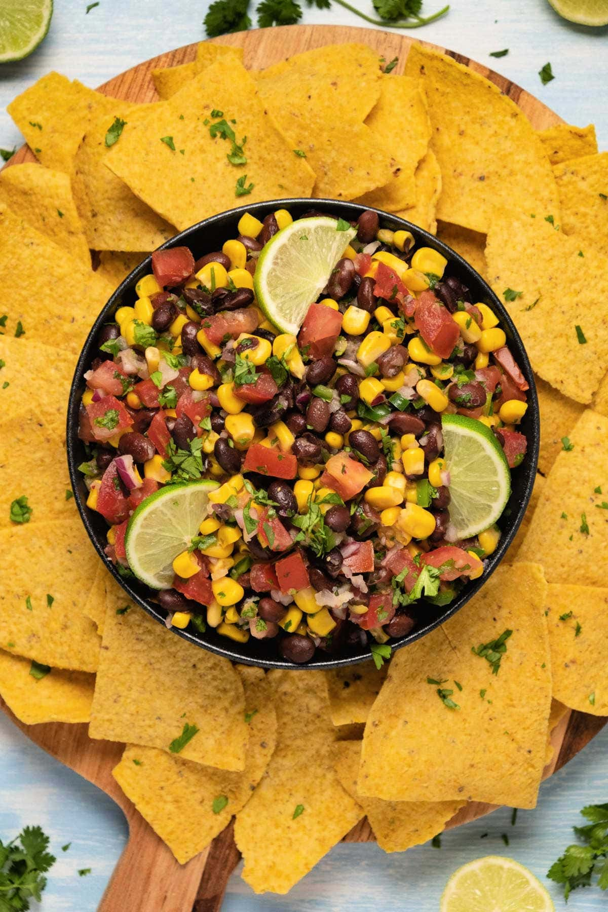 Black bean salsa in a black bowl with fresh lime slices.