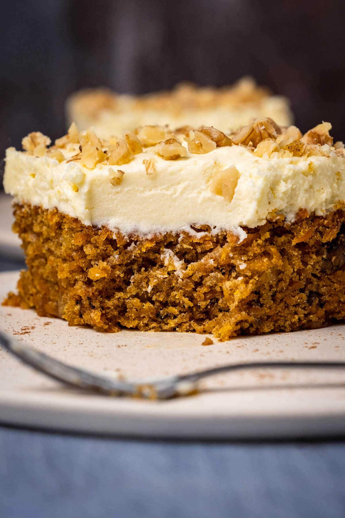 Slice of carrot cake on a white plate with a cake fork.