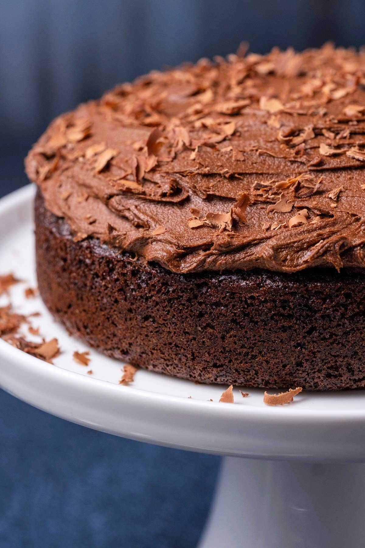 Photo of a small chocolate cake on a white cake stand.