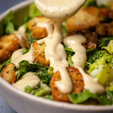 Vegetarian caesar dressing drizzling off a spoon over a caesar salad.