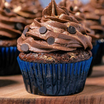 Eggless chocolate cupcakes on a wooden board.