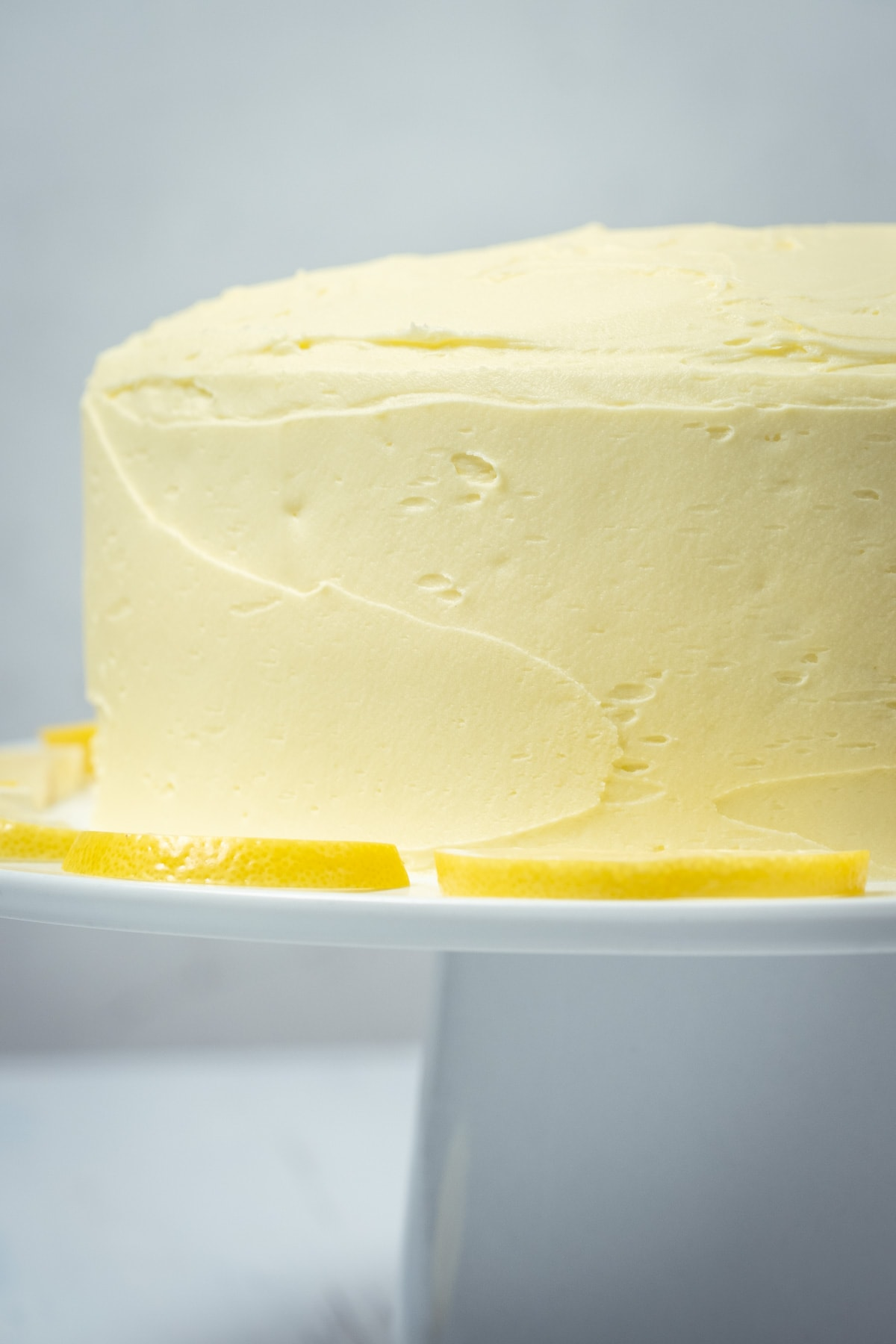 Frosted lemon cake on a white cake stand.