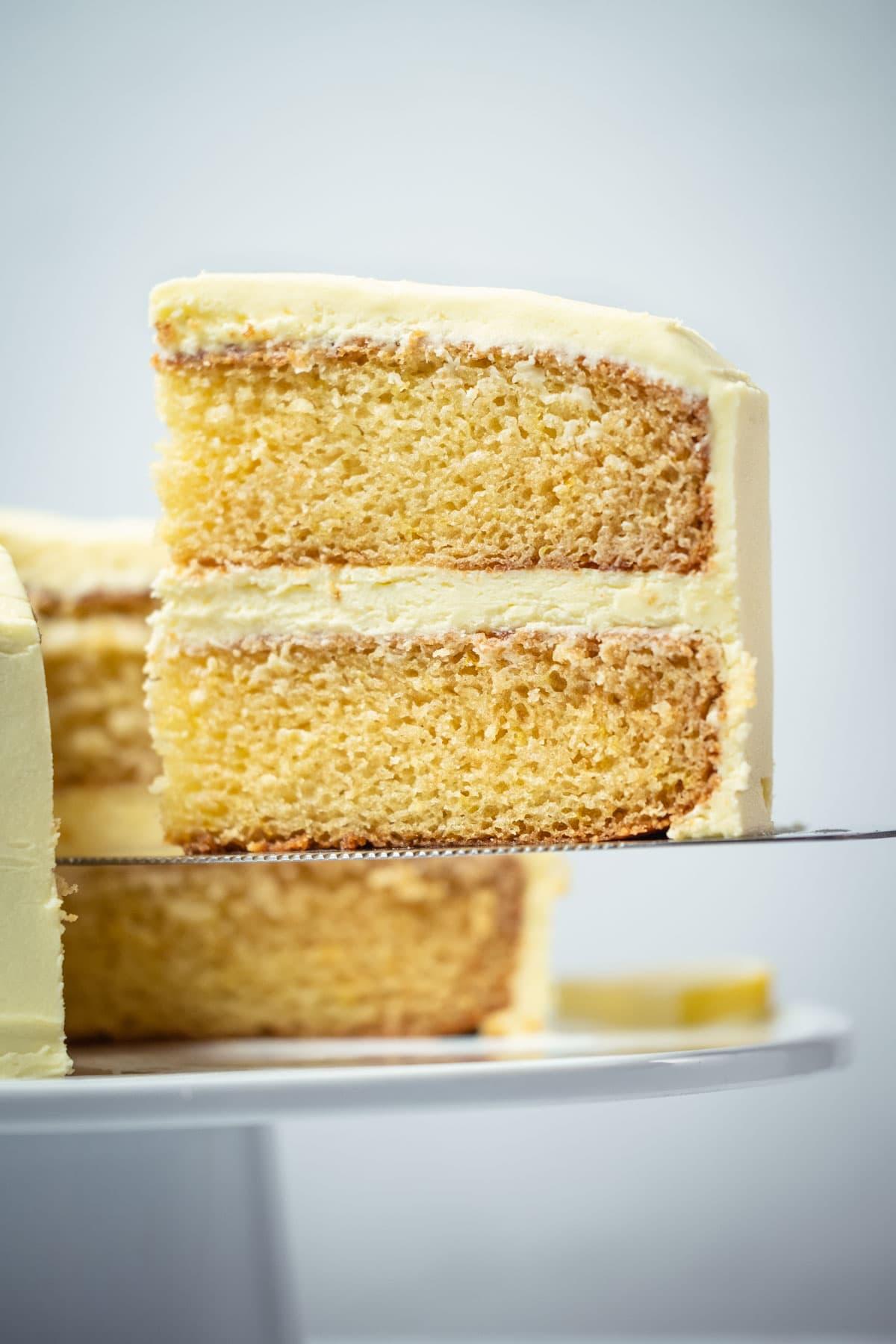 Slice of eggless lemon cake on a cake lifter.