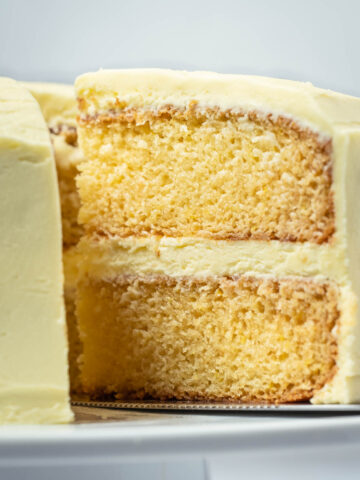 Eggless lemon cake on a white cake stand with one slice cut and ready to be served.