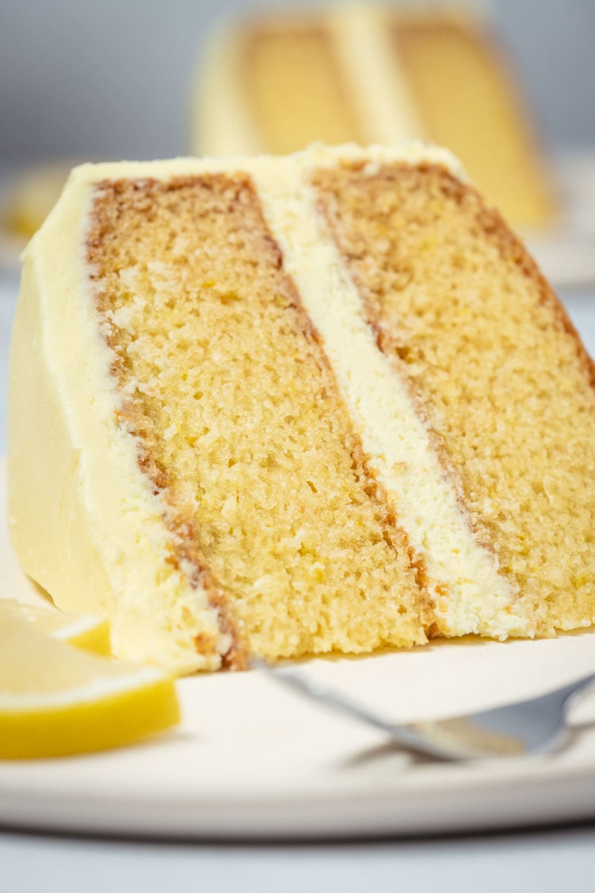 Slice of eggless lemon cake on a white plate with a cake fork.