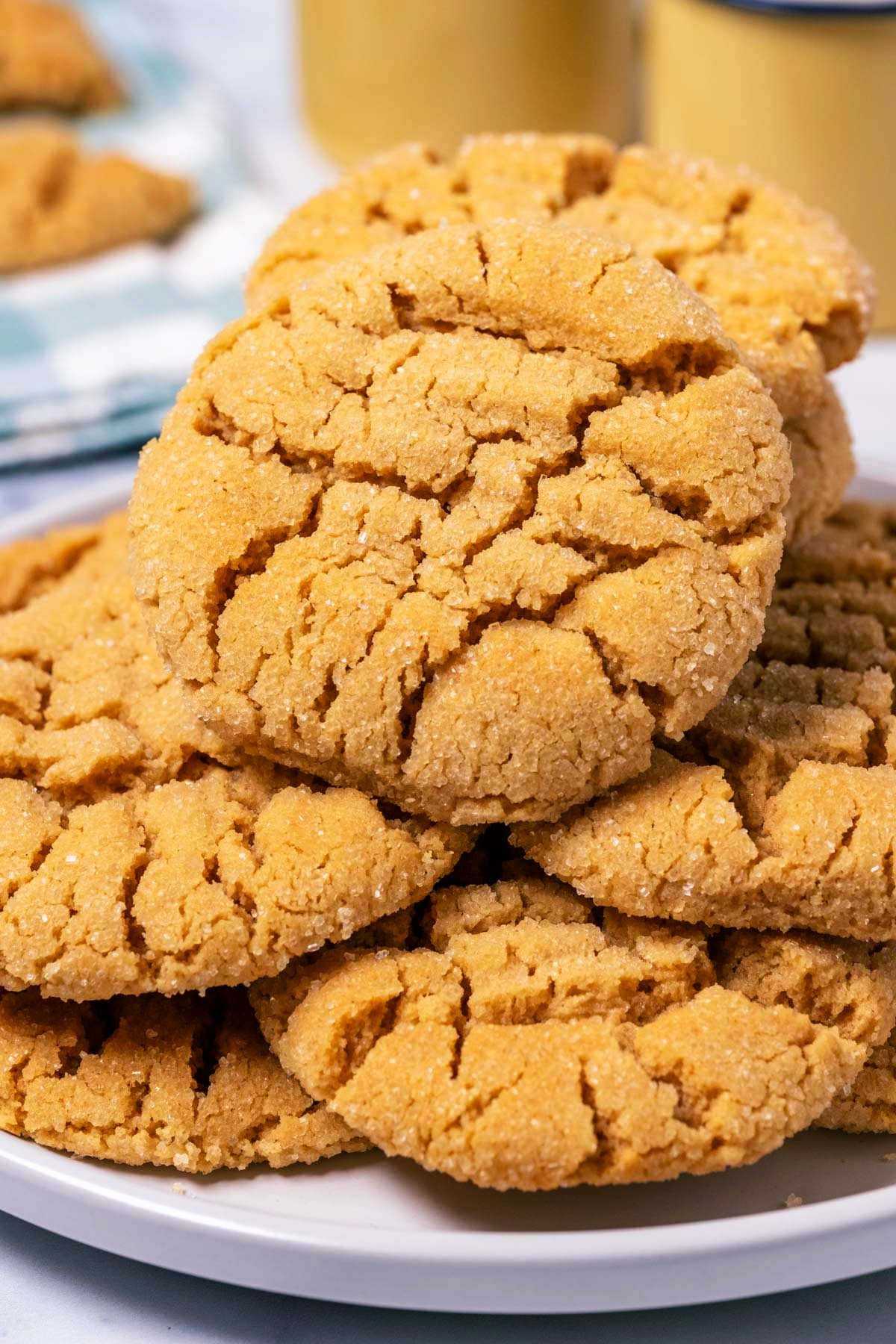 Eggless peanut butter cookies stacked up on a white plate.