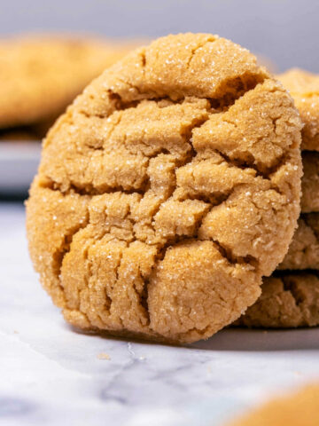 Peanut butter cookie leaning against a stack of cookies.