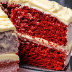 Eggless red velvet cake on a white cake stand with one slice cut and ready to serve.