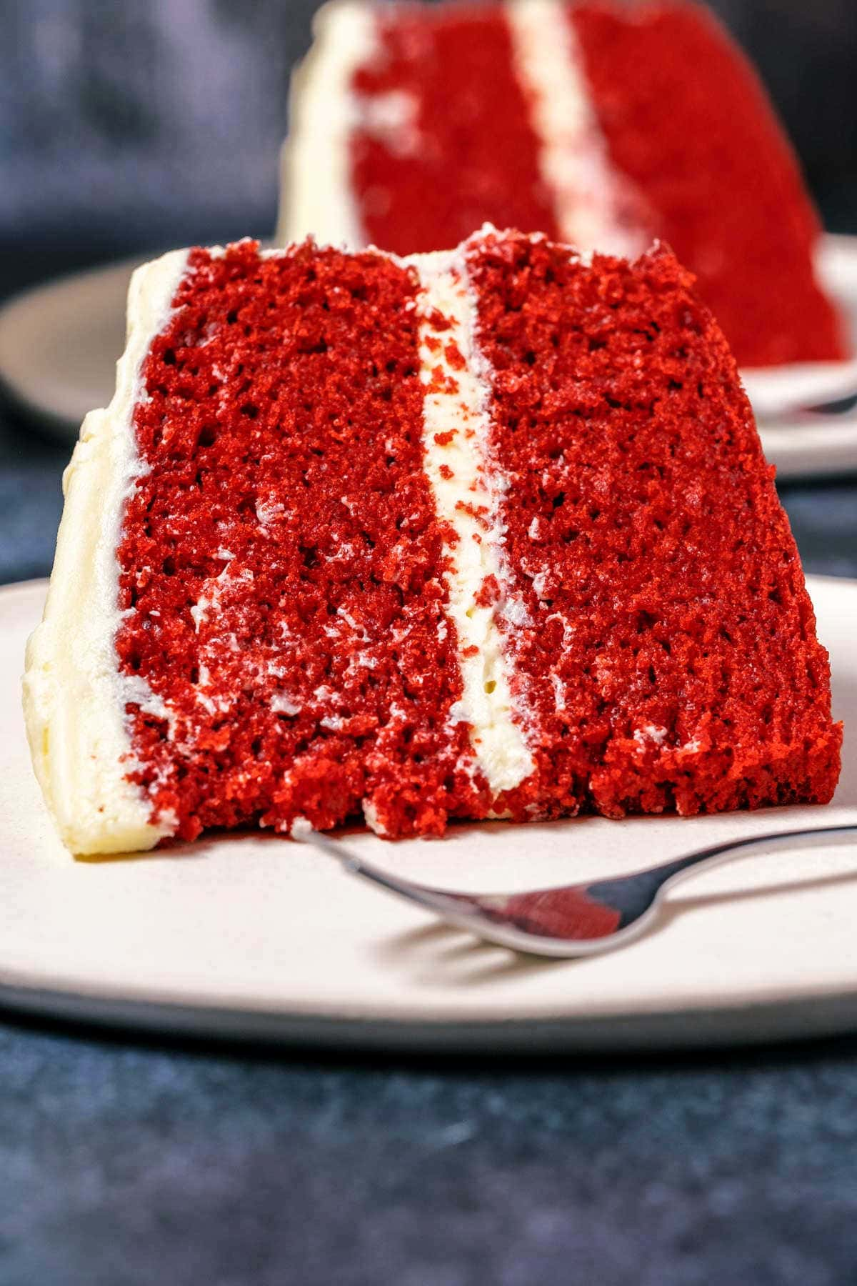 Slice of eggless red velvet cake on a white plate with a cake fork.