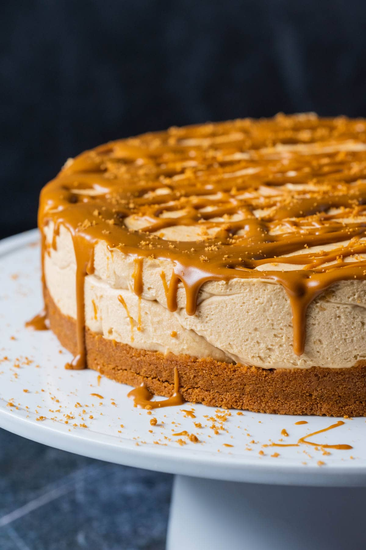 Biscoff cheesecake on a white cake stand.