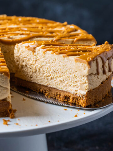 Biscoff cheesecake on a white cake stand with one slice cut and ready to serve.