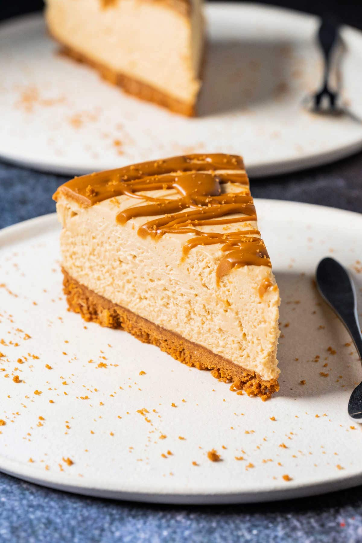 Slice of biscoff cheesecake on a white plate with a cake fork.