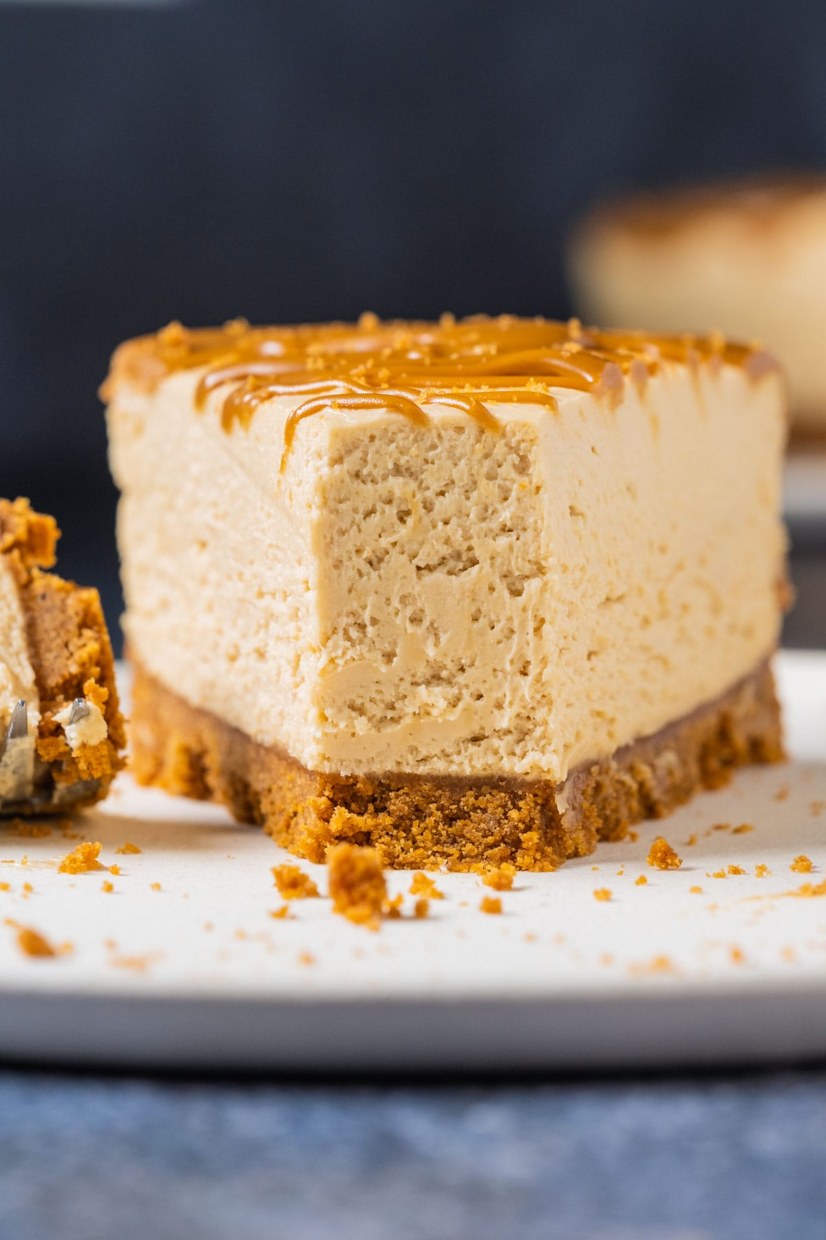 Slice of biscoff cheesecake on a white plate.