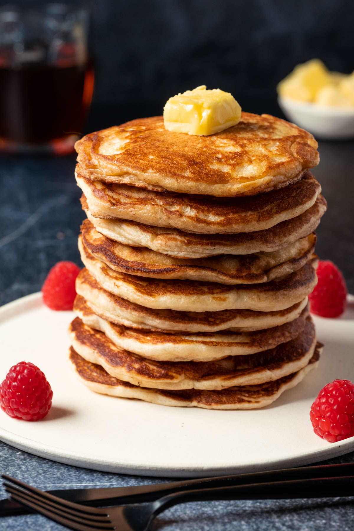 Stack of eggless pancakes topped with a knob of butter on a white plate.