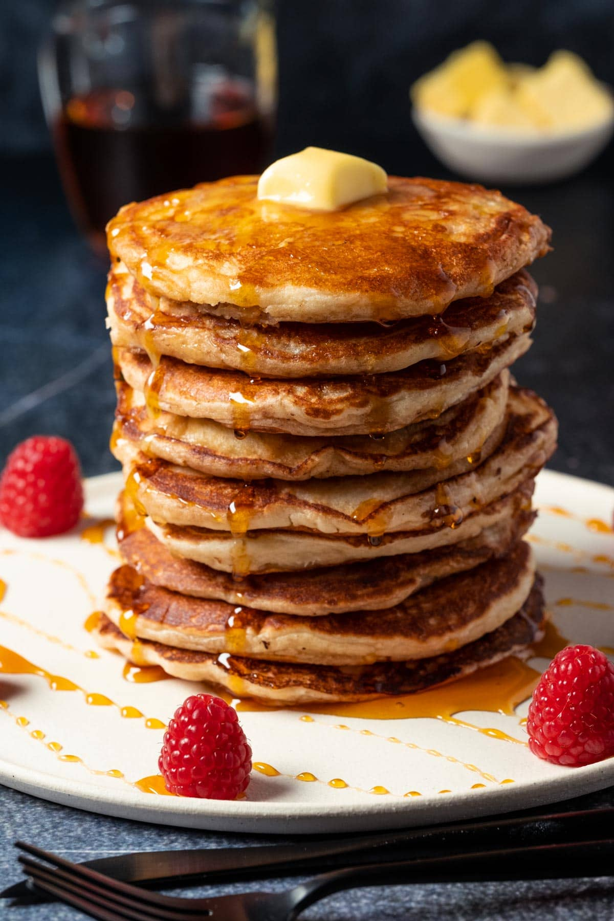 Stack of pancakes topped with butter and drizzled with syrup, on a white plate.
