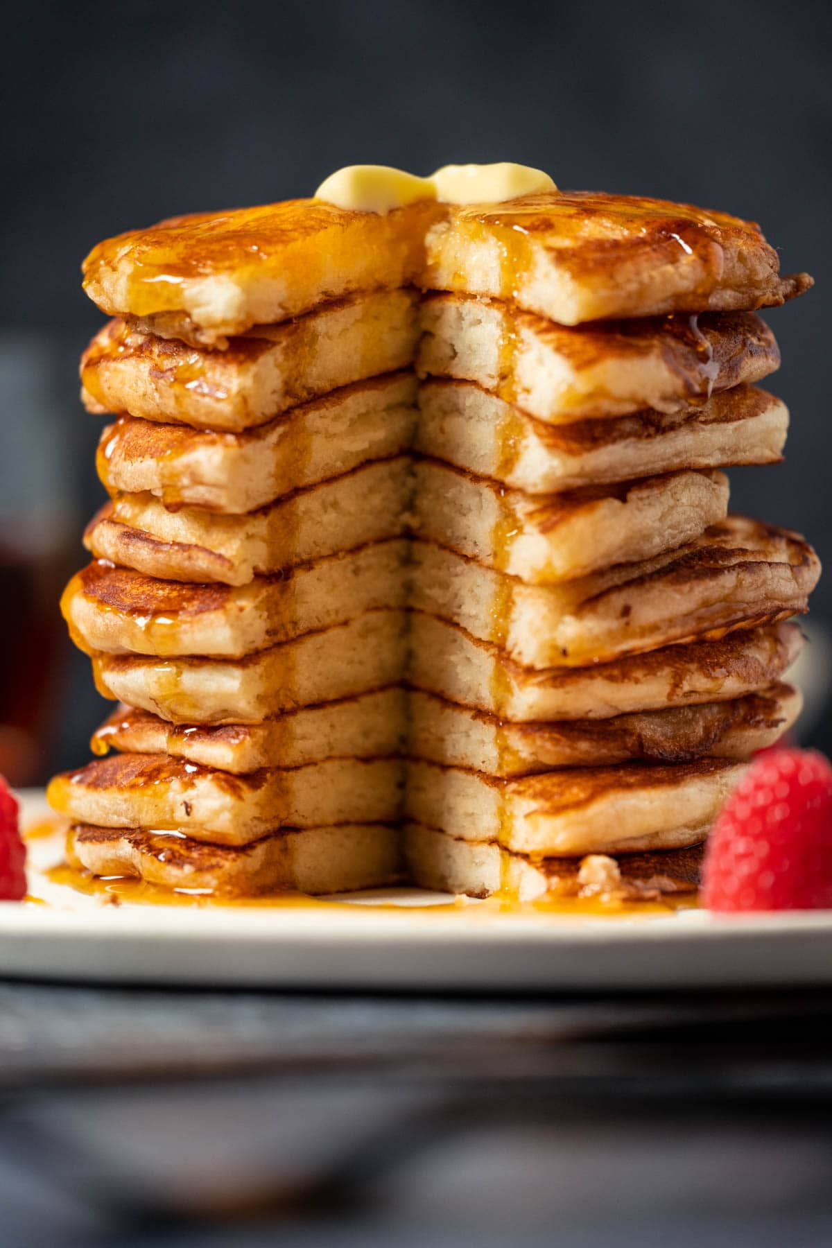 Stack of pancakes with a section cut out, on a white plate.