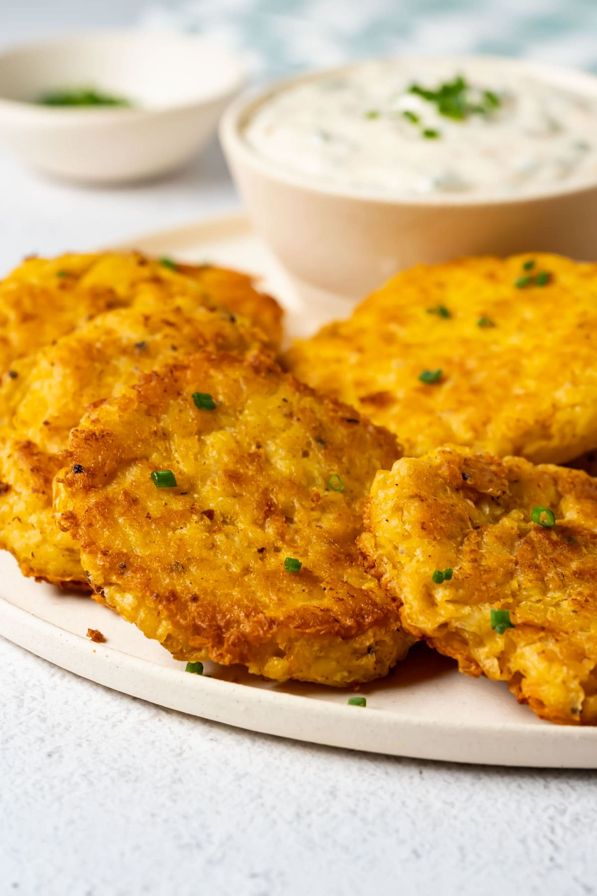 Potato fritters on a white plate with garlic dip.