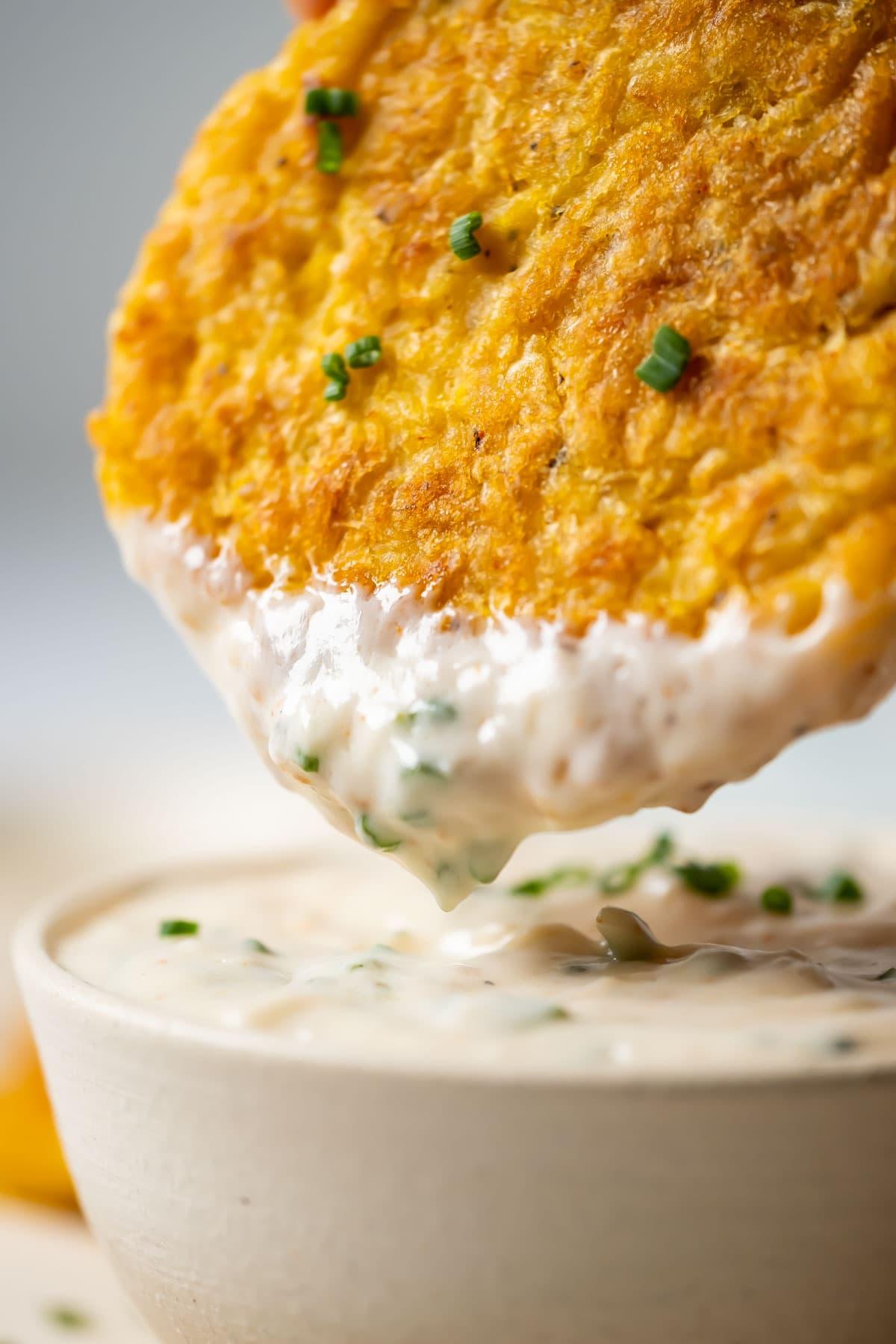 Potato fritter dipping into garlic dip.