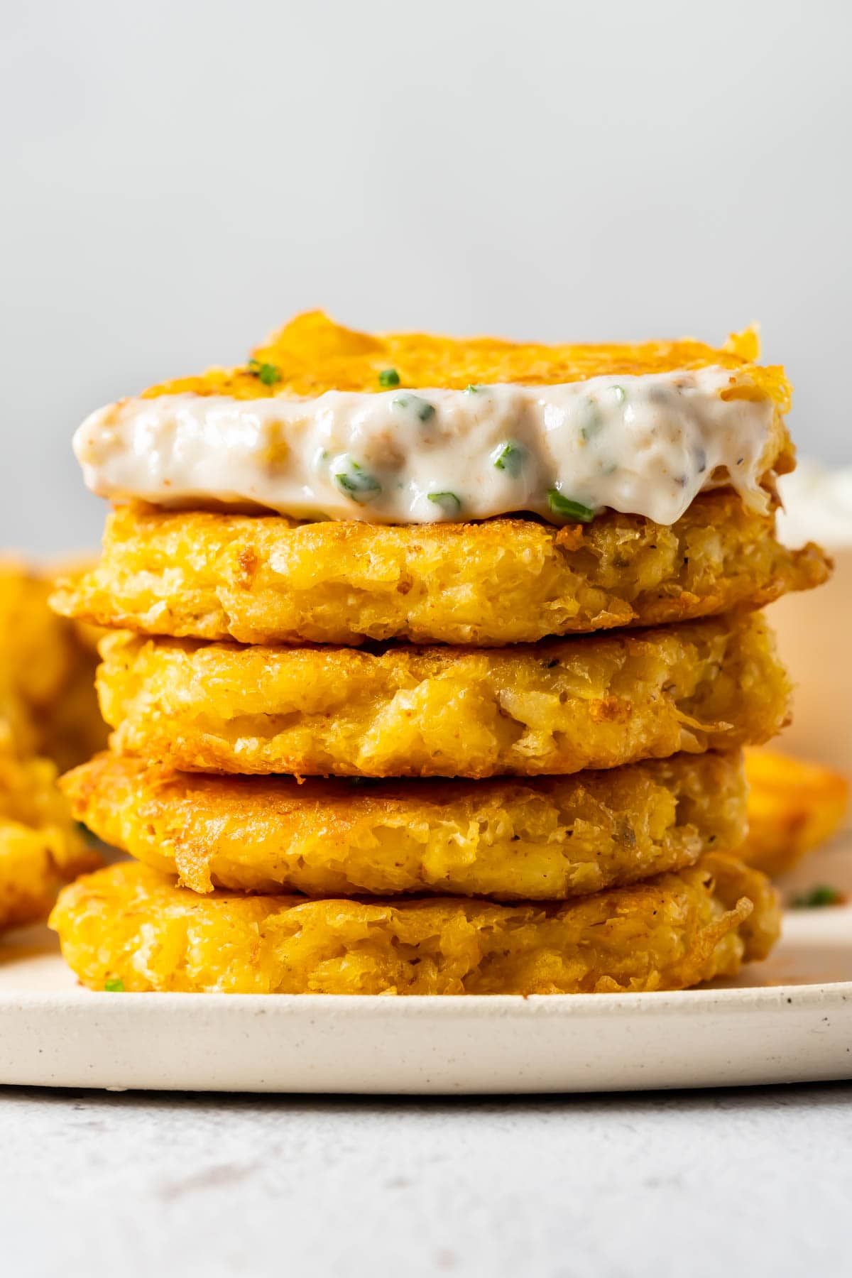 Stack of potato fritters on a white plate.