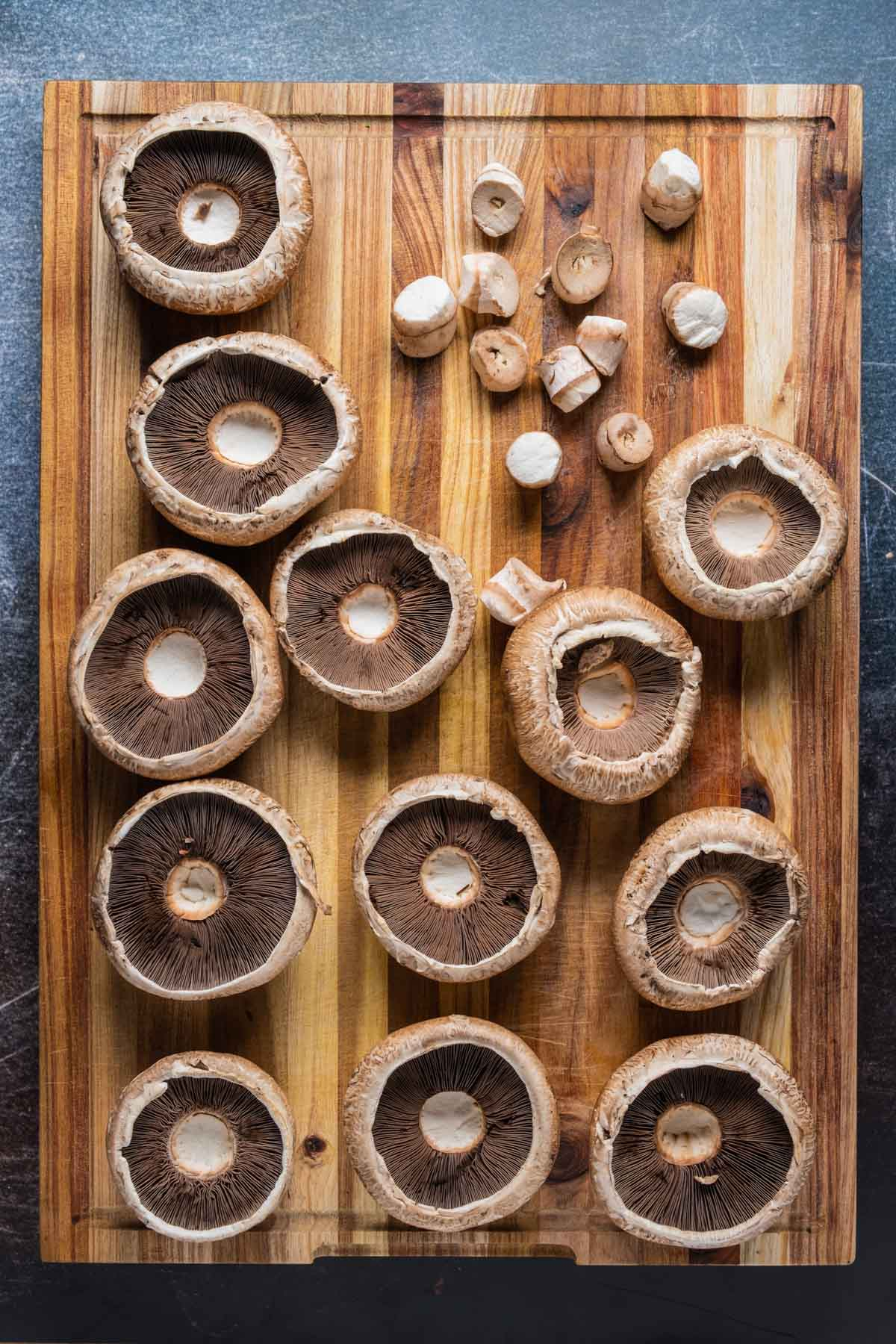 Mushrooms with stems removed on a wooden board.