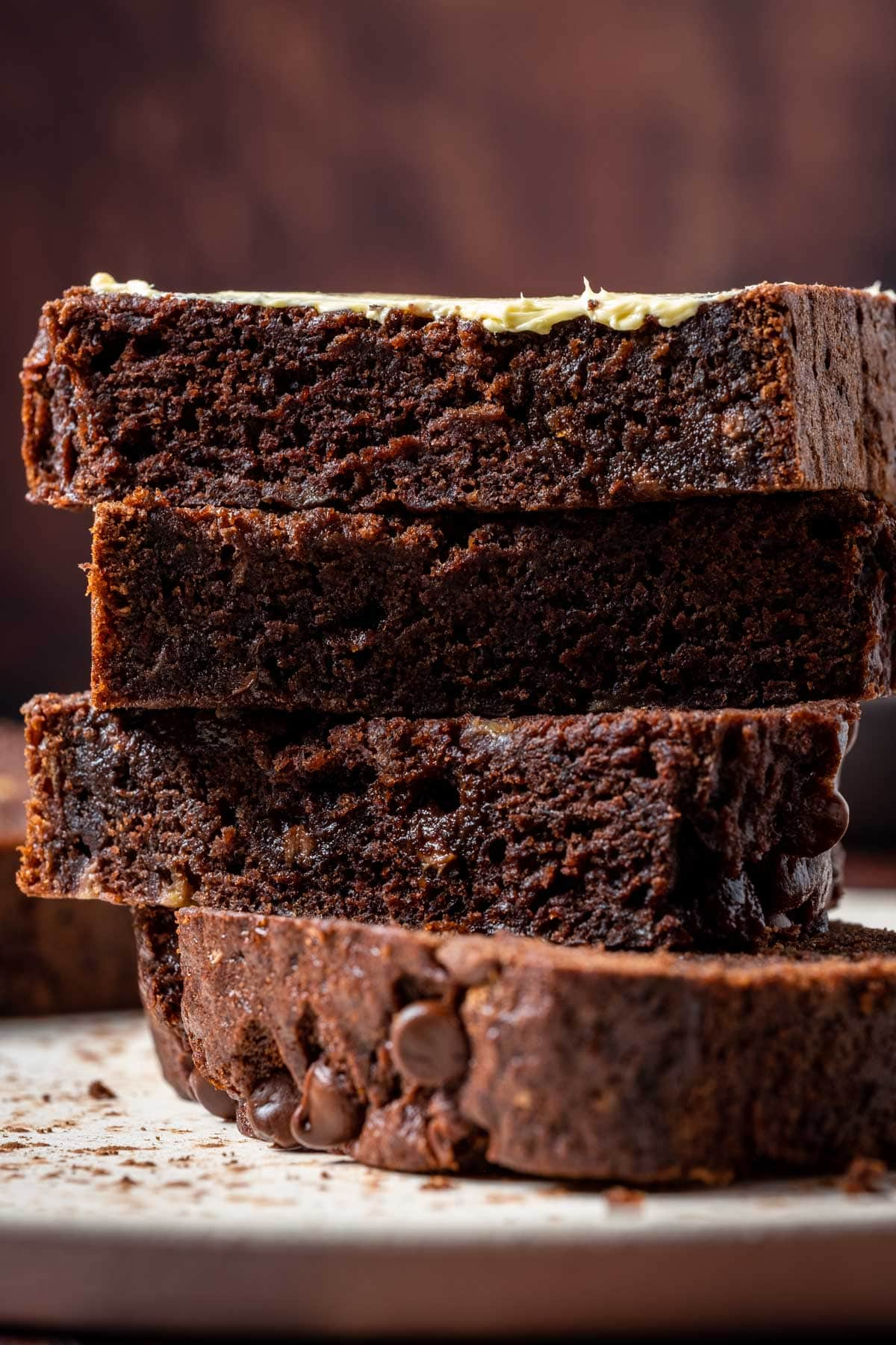 Slices of double chocolate banana bread stacked up on a white plate.