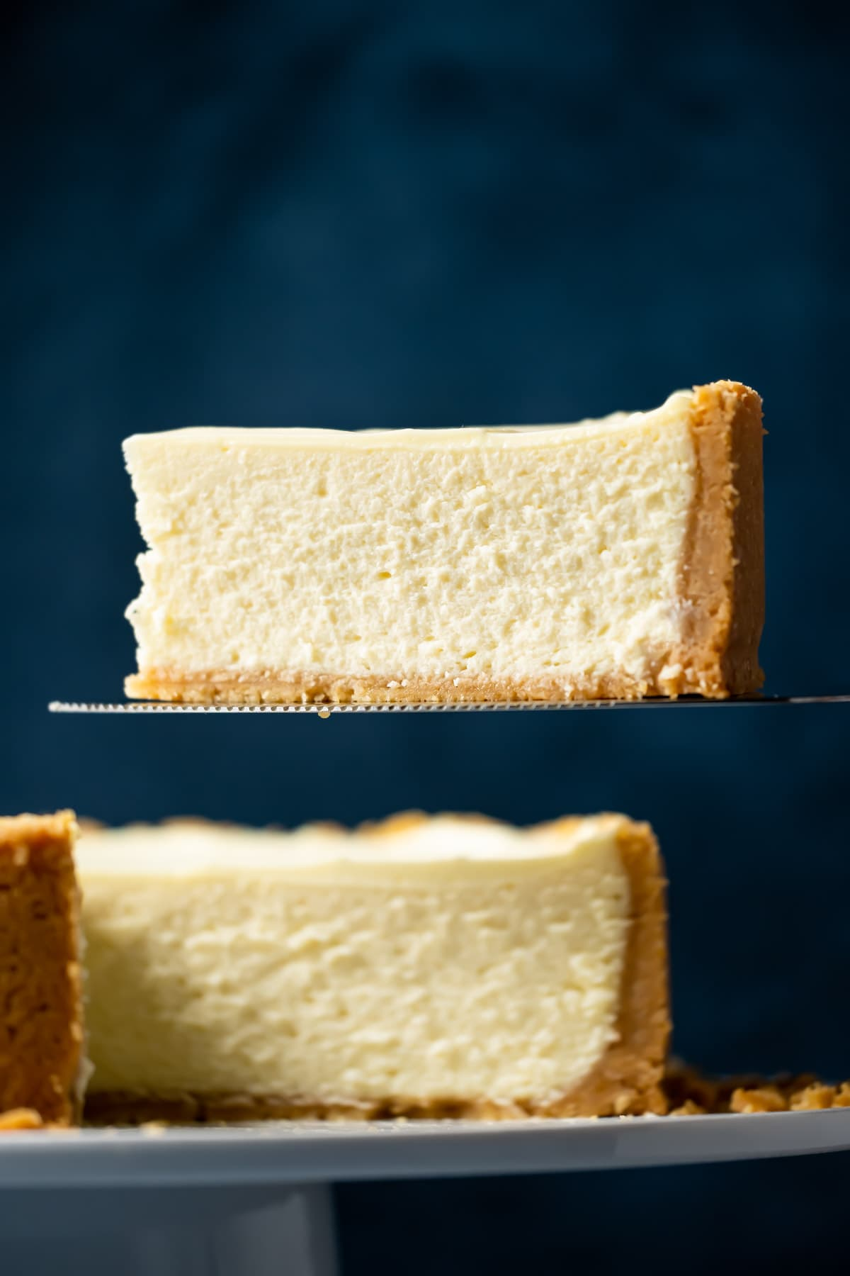 Slice of eggless cheesecake on a cake lifter.