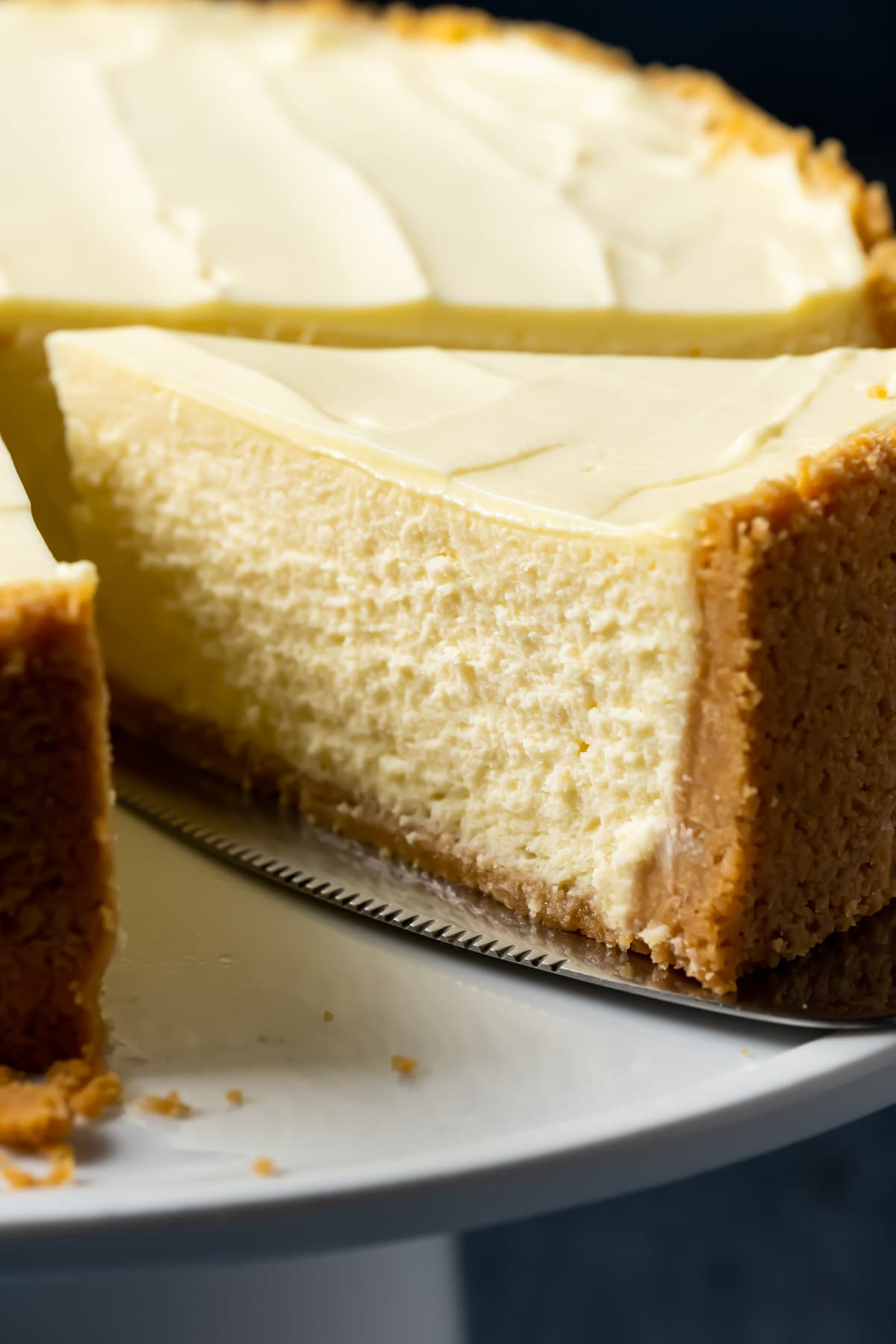 Eggless cheesecake on a white cake stand with one slice ready to serve.