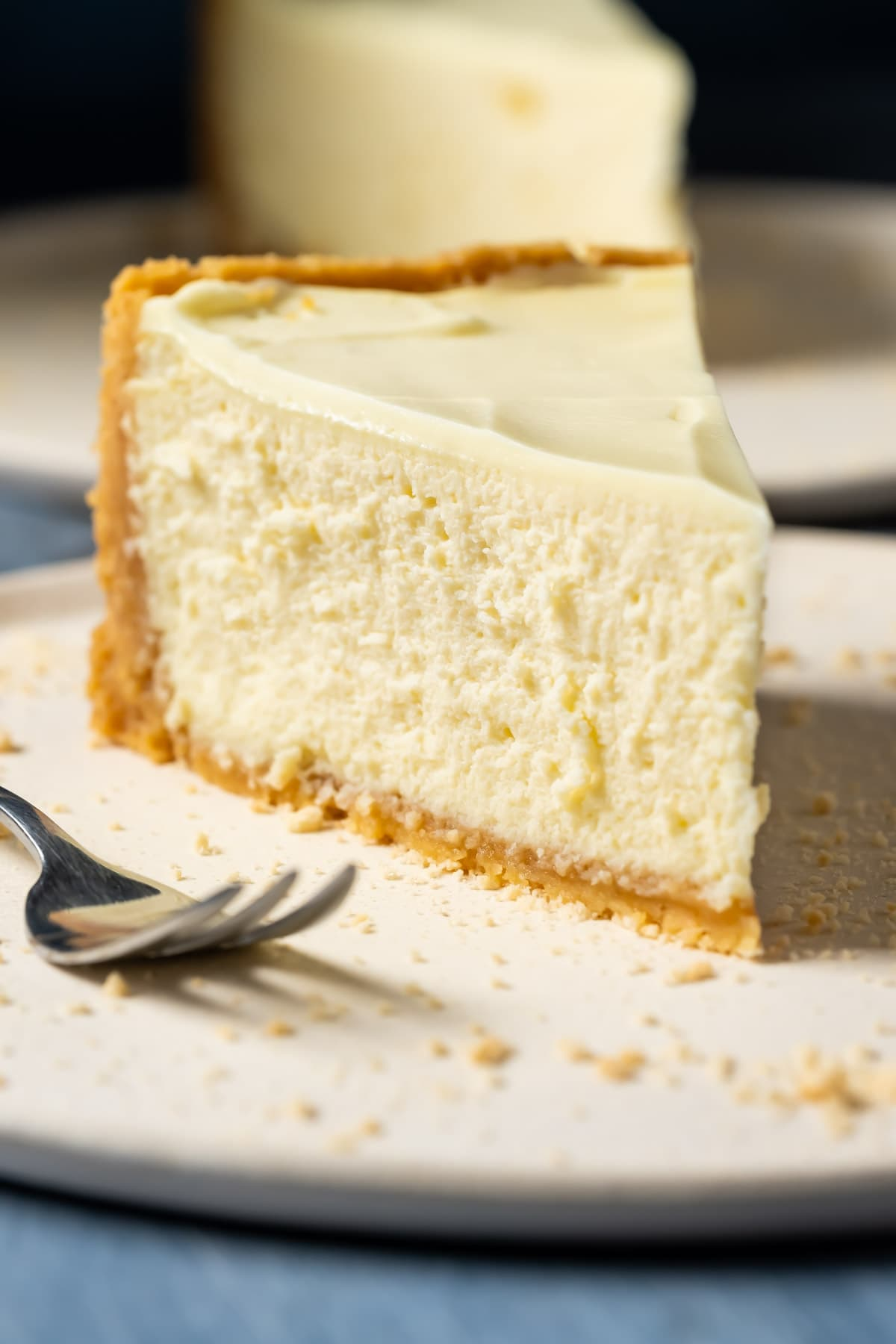 Slice of eggless cheesecake on a white plate with a cake fork.