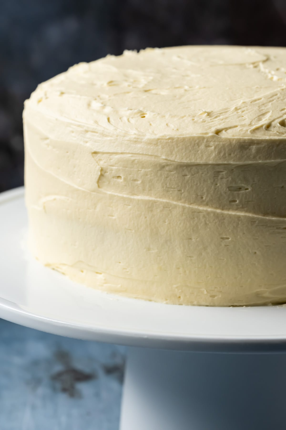 Frosted vanilla cake on a white cake stand.