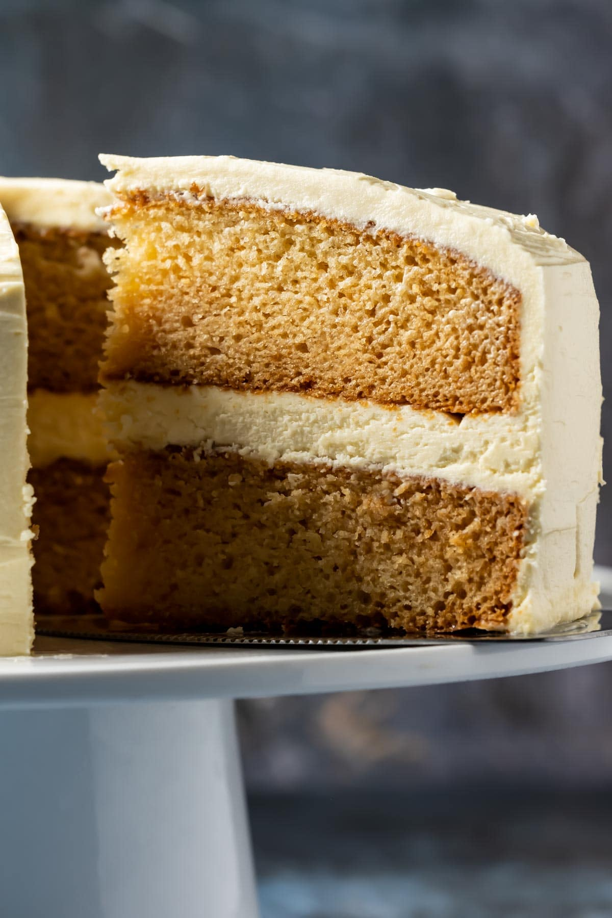 Vanilla cake on a white cake stand with one slice cut and ready to serve.