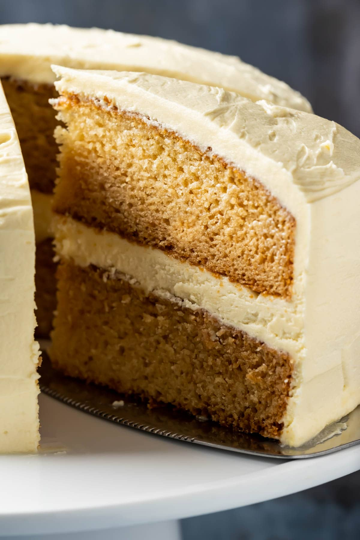 Slice of eggless vanilla cake on a cake lifter, ready to serve.