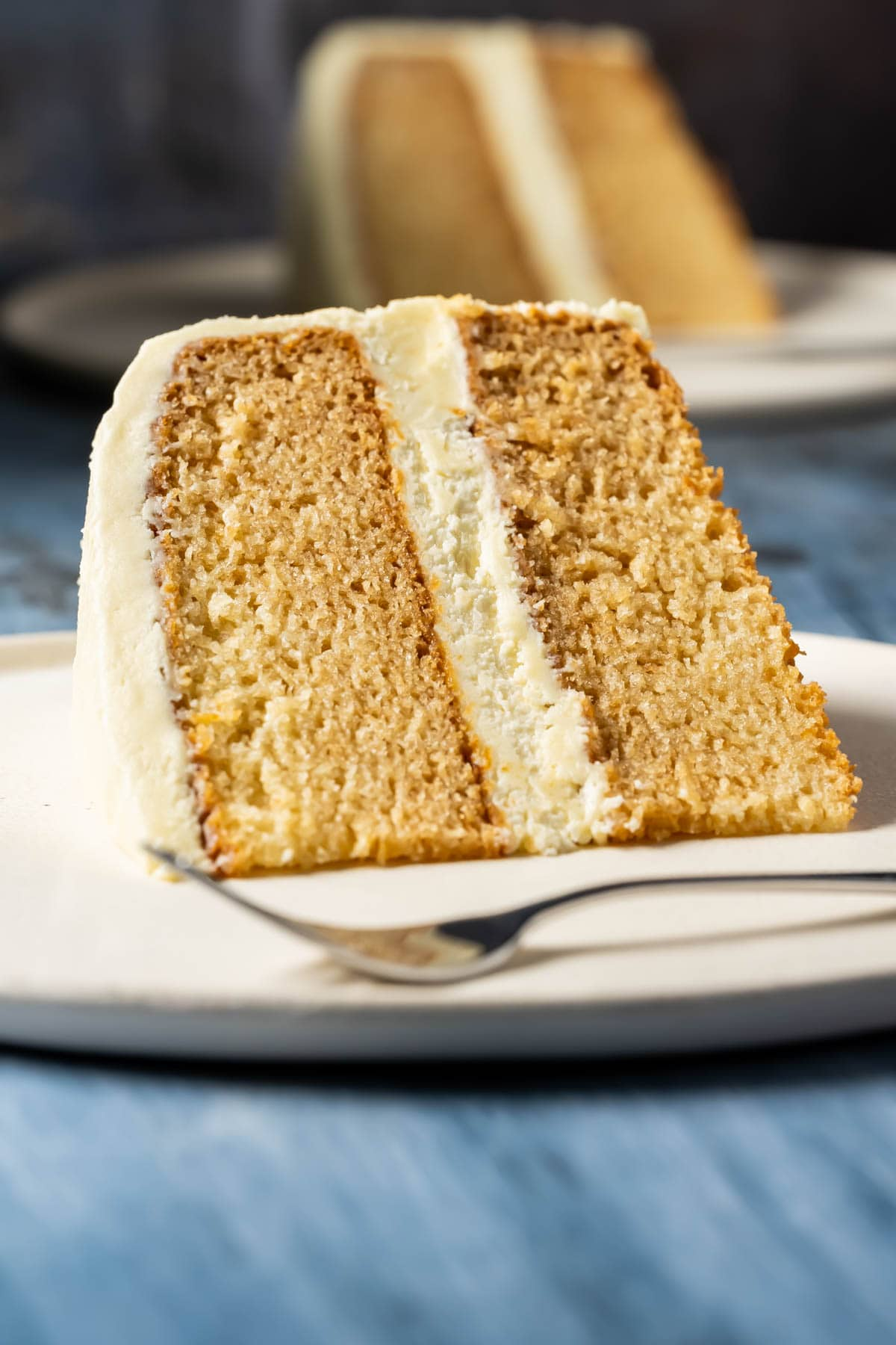 Slice of eggless vanilla cake on a white plate with a cake fork.