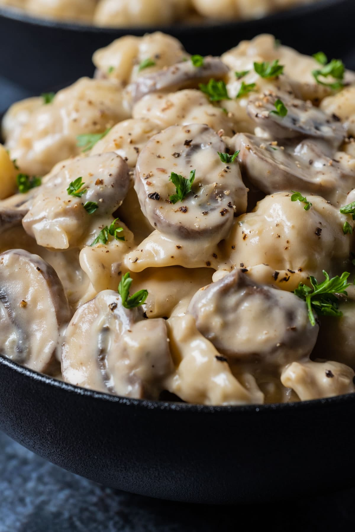 Vegetarian stroganoff topped with fresh chopped parsley in a black bowl.