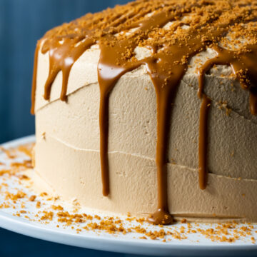 Frosted biscoff cake with drizzled biscoff cookie butter on a white cake stand.
